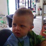 Enfant aux cheveux mi-long blond et court
